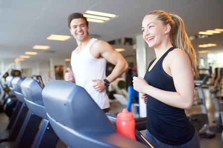 fitness hombres: Saludable Pareja joven que hace ejercicio corriente de la rueda de ardilla de dispositivos dentro del gimnasio con felices expresiones faciales. Foto de archivo