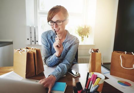 trabjando en casa: Mujer joven que trabaja en casa en su computadora portátil, Oficina pequeña
