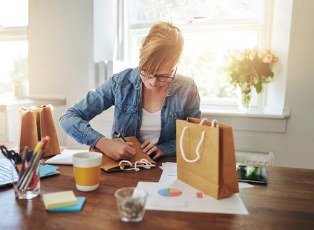 Jonge onderneemster het ontwerpen van verpakkingen voor haar nieuwe start-up online business zit aan haar bureau thuis werken op een gift bag