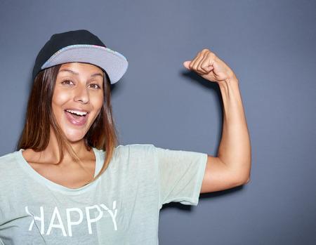 Speelse jonge vrouw pompen haar spieren buigen haar arm om te pronken met haar biceps met een glimlach lachen, over grijs