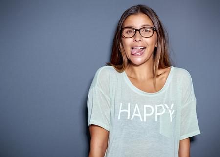 adentro y afuera: Mujer asiática joven que llevaba gafas y una camiseta informal sacando la lengua a la cámara en un gesto lúdico o grosero, sobre gris con copyspace