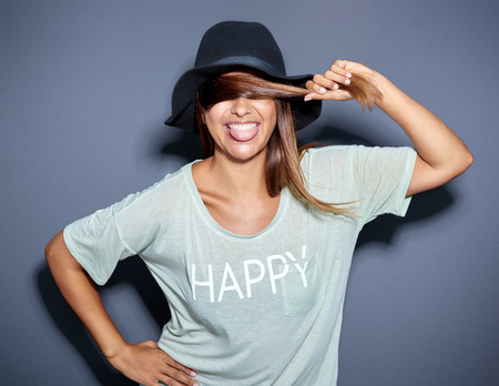 laughing face: lively happe young woman in a trendy hat sticking out her tongue with a laughing smile as she holds a strand of her hair across her eyes Stock Photo