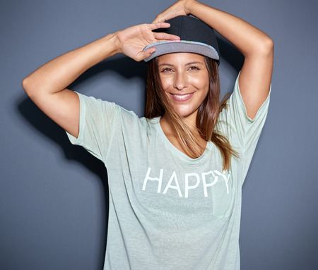 Pretty young Asian woman wearing a trendy baseball cap and summer t-shirt looking at the camera with a gorgeous smile, over grey Stock Photo