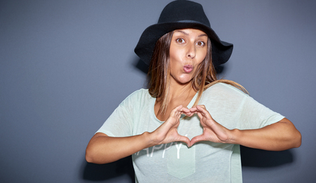 puckering lips: Playful romantic young woman making a heart gesture with her fingers while puckering up her lips for a kiss, over grey with copyspace