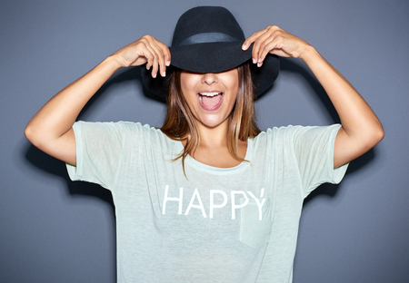 Fun portrait of a young woman in a trendy wide-brimmed hat laughing as she flips the brim over her eyes