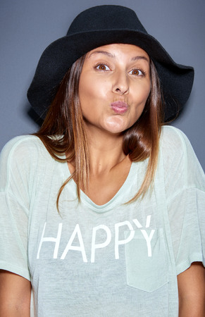 puckering lips: Teasing attractive young woman in a fashionable wide brimmed hat puckering up her lips asking for a kiss with an amused expression