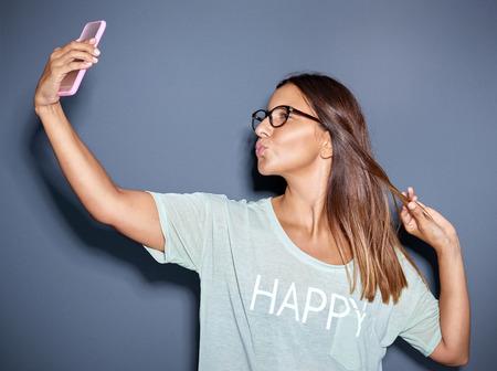 profil: Młoda kobieta stwarzających w zabawny selfie jak ona wybrzusza się usta do pocałunku w sposób dokuczanie na kamery na jej telefon komórkowy