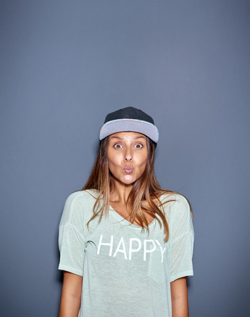 grey eyed: Funny young woman with a look of wide eyed surprise or amazement pursing up her lips as she looks at the camera, with copyspace on grey above Stock Photo