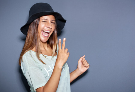 ethnic woman: Excited young woman making a V-sign gesture with her hand as she stands sideways winking at the camera in a fun portrait over grey with copyspace