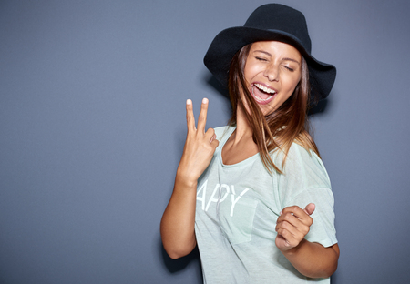mouth closed: Hipster fashionable young woman giving a playful V-sign gesture as she laughs and jokes with the camera in her trendy hat, over grey with copyspace Stock Photo
