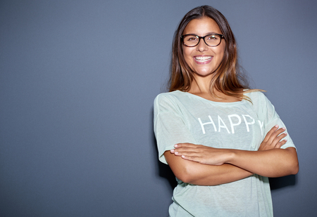 jaunty: Jaunty Confiado Mujer atractiva joven con gafas de pie con los brazos cruzados dando a la c�mara con una sonrisa cursi, sobre gris con copyspace Foto de archivo