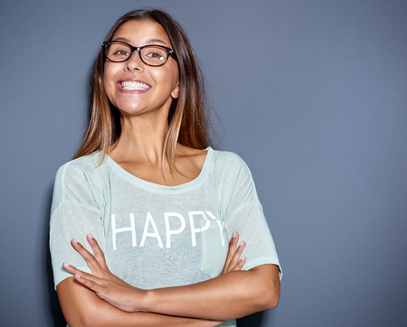 cheesy grin: Lively attractive young Asian woman wearing glasses with a big cheesy grin standing with folded arms smiling at the camera, over grey Stock Photo
