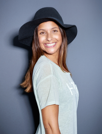 Cute young woman with a big beaming smile wearing a trendy felt hat standing grinning at the camera over grey in a fun humorous portrait