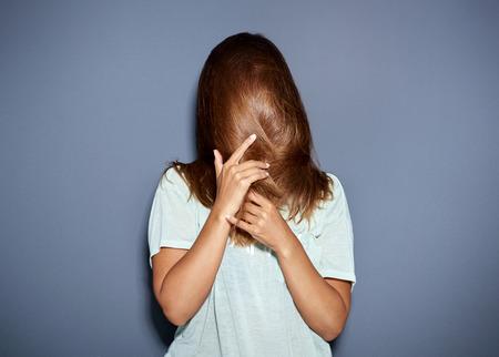 discreto: Diversión retrato de una mujer que oculta detrás de su pelo largo y castaño mientras se tira de ella hacia abajo sobre la cara con las manos, cuerpo superior sobre gris