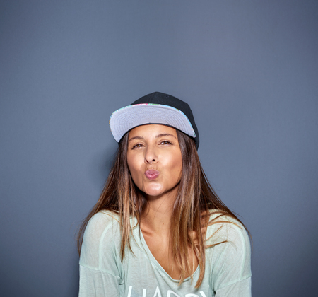 tantalizing: Lively woman kissing at the camera while wearing a cap Stock Photo