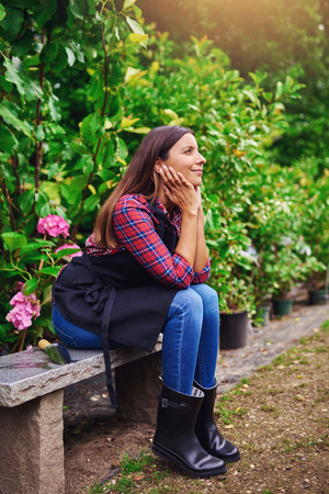 reverie: Pretty young nursery worker sitting on a wooden bench daydreaming with a smile of pleasure on her face as she takes a break in the greenhouse from attending to the plants
