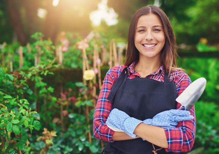 smiling woman in a greenhouse: Smiling successful young nursery owner standing amongst her plants with folded arms and a trowel in her hands beaming at the camera