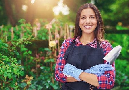 garderie: Sourire réussie jeune propriétaire de la pépinière debout au milieu de ses plantes, les bras croisés et une truelle dans ses mains rayonnant à la caméra