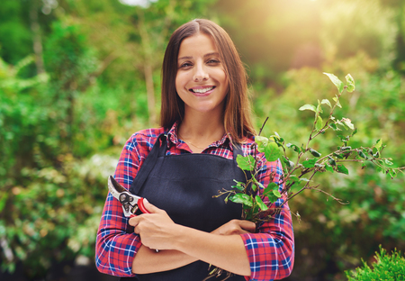 pruning shears: Smiling young female gardener pruning the plants standing in a lush green garden with a apir of secateurs in her hand smiling at the camera