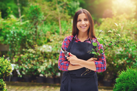 Happy confident attractive young woman pruning plants in a nursery as she celebrates her success as an entrepreneur with her own business Archivio Fotografico