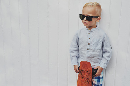 confident: Serious trendy little boy posing with his skateboard wearing a pair of over sized stylish sunglasses borrowed from his father looking towards blank copyspace on a white wall