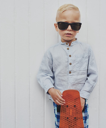 borrowed: Serious small boy in modern fashionable sunglasses borrowed from his Dad standing holding his skateboard in front of a white wall looking at the camera Stock Photo