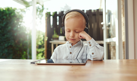 immersed: Cute young boy immersed in his music sitting listening on stereo headphones attached to a tablet with his head resting on his hand and a smile of bliss