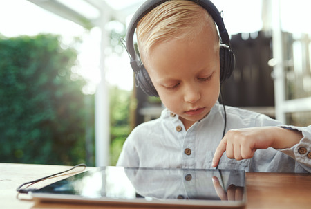 pensive: Pensive little boy selecting a new soundtrack from his music library on his tablet computer as he sits outdoors on a patio listening to music on stereo headphones Stock Photo