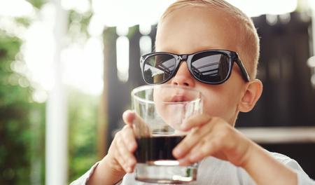 gaseosas: Lindo inconformista niño pequeño en más de gafas de sol de tamaño pertenecientes a su madre o padre sentado bebiendo una bebida en un vaso sobre un patio al aire libre