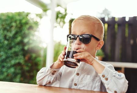 gaseosas: niño pequeño con estilo con gafas de sol de moda pertenecientes a su mamá o papá que se sientan en un patio al aire libre bebiendo un refresco de un vaso mientras se juega a ser adulto