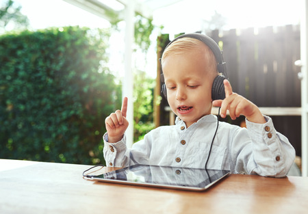 conducts: Little boy immersed in his music gesturing with his hands as he conducts and sings along to the lyric and beat on his headphones as he sits at a table on a patio at home Stock Photo
