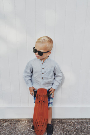 borrowed: Cute little boy in a trendy summer outfit posing with his skateboard against a white wall in a pair of sunglasses borrowed from his mother or father