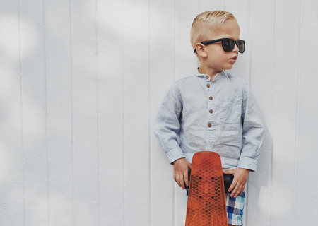 Cute little guy in big trendy sunglasses that he has borrowed from his mother or father posing with his skateboard against a white wooden wall with copyspace