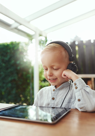 downloaded: Little boy smiling in delight as he listens to music downloaded on his tablet-pc using stereo headphones while sitting outdoors on an open-air patio on a hot summer day