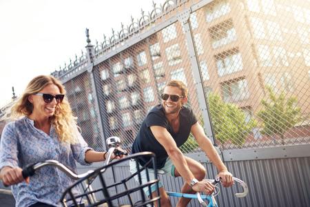 幸せな若いカップルを楽しむ夏自転車に乗って笑って、冗談は彼らは一緒に輝く日光都市通りをサイクルとして