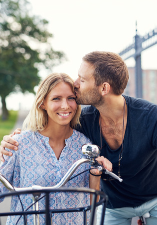 flattered: Affectionate young man kissing his girlfriend on the forehead as they enjoy a summer day in the fresh air on their bicycles