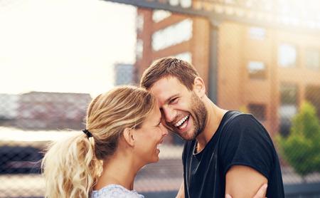幸せな自発的な魅力的な若いカップルは大笑いと屋外都市環境でお互いをハグ良いジョークを共有します。