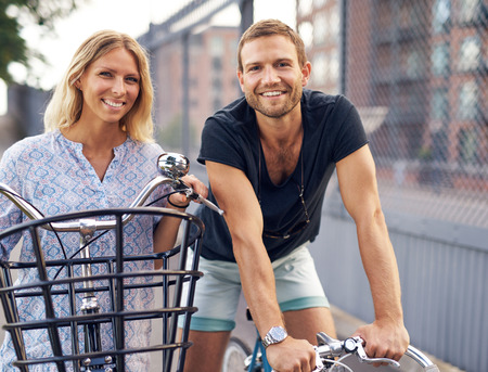 Fit young couple out enjoying a day cycling on their bicycles standing looking over the handlebars smiling at the camera Stock Photo