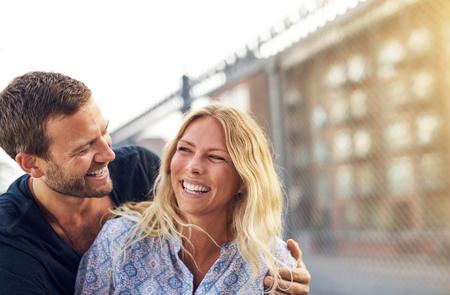 romantico: Feliz vivaz joven pareja romántica disfrutando de un buen abrazo broma y riendo alegremente como están al aire libre en la mañana urbana calle residencial Foto de archivo