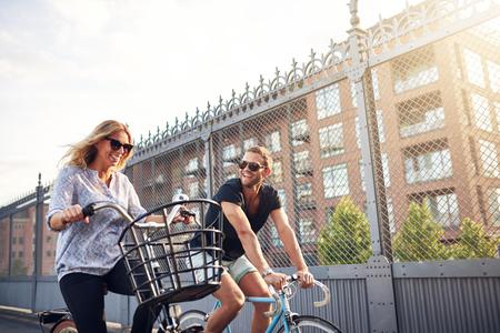 sunshine: Feliz pareja sana en un paseo en bicicleta el fin de semana en bicicleta por una calle urbana en sol del verano en sus bicicletas, vista de �ngulo bajo Foto de archivo