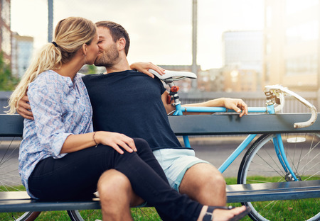 smooching: Young couple relaxing on an urban bench enjoying a romantic loving kiss with their bicycles behind them and sun flare