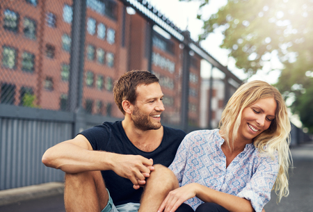 turn away: Man teasing his girlfriend, big city couple in a park