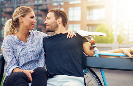intimacy: Loving couple sitting on bench in a city environment