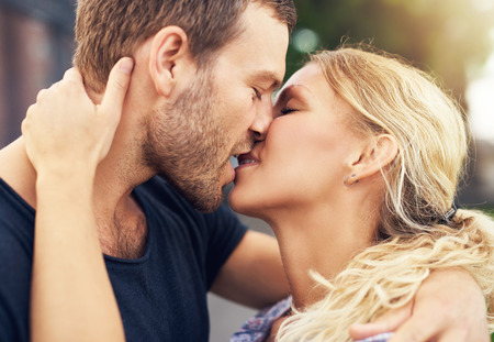 parejas romanticas: Pareja joven profundamente en el amor que comparte un beso rom�ntico, primer plano vista de perfil de la cara