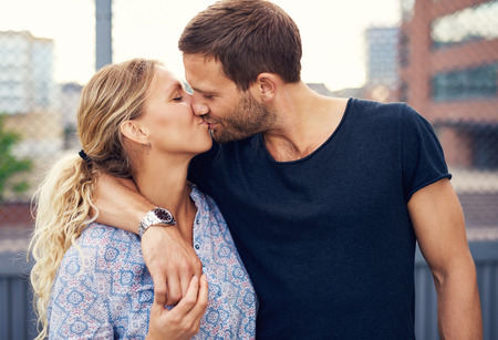 arm: Amorous attractive young couple enjoy a romantic kiss as they stand arm in arm outdoors in an urban street Stock Photo
