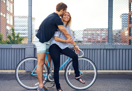 courting: Sweet Young Couple on a Bicycle at the City Street Against Metal Fence Background. Stock Photo