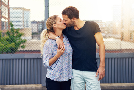 demonstrative: Loving demonstrative handsome young man kissing his girlfriend as they stand in a close embrace on an urban street Stock Photo