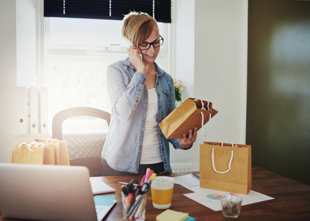 home business: Motivated businesswoman placing orders on the phone for the packaging for her new online web based store as she holds a brown paper gift bag in her hand