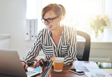 Successful female entrepreneur with a new online business working from home on her computer typing in data