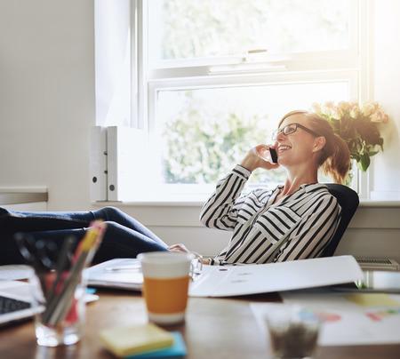 Glückliche junge Geschäftsfrau im Gespräch mit jemandem über ihr Handy beim Entspannen im Büro mit den Beinen auf ihrem Schreibtisch.
